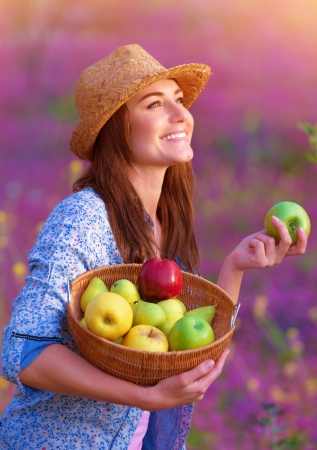 Portrait of happy woman with basket of apples on pink floral field, enjoying tasty ripe fruits, working in garden, harvest concept photo