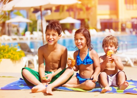 summertime: Three kids sitting down and eating croissant near pool, picnic outdoors, beach resort, summer vacation, happy childhood concept