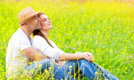 Happy couple sitting down on fresh yellow floral field, romantic date, hugging outdoors, loving family, romance and enjoyment concept photo