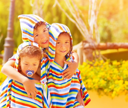 Closeup portrait of three funny child wearing same colorful clothing, beach towels, happy family hugging outdoors, summer holidays concept Stock Photo - 21234264