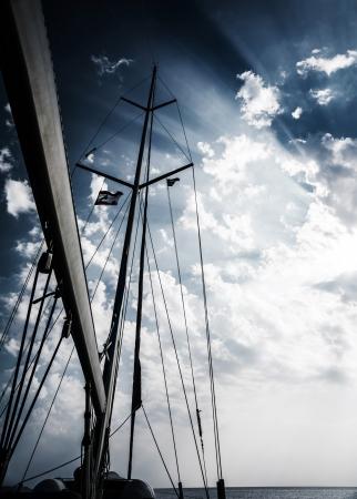 濃い曇り空を背景に海、セーリング スポーツ、ドラマチックな日没、水輸送、悪天候の中の嵐のヨットのマスト