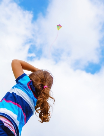 Little girl looking up in the sky on beautiful colorful air kite, rear view, enjoying summer game, flying toy, happy childhood concept