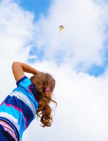 Meisje opzoeken in de lucht op mooie kleurrijke lucht vlieger, achteraanzicht, genieten van de zomer spel, vliegend speelgoed, gelukkige jeugd begrip