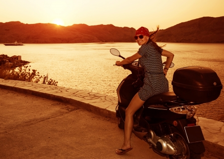 moto: Happy prety woman on motorcycle on sunset light near sea, summer adventure, drive motorbike, active lifestyle, travel and tourism concept