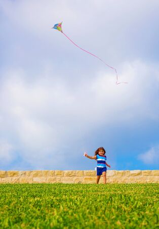 Sweet little girl running with kite on green field, adorable child having fun on backyard, playing game with windy paper toy outdoors, happiness concept photo
