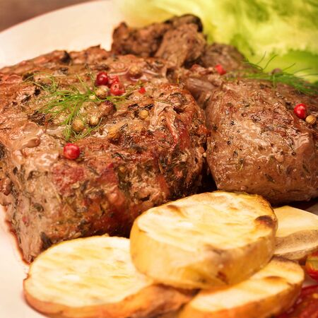 Tasty grilled meat with baked potato on the plate, medium roasted beefsteak with spice, organic food, restaurant menu photo