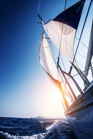 Sail boat in action, summer adventure, luxury water transport, sunset light, active lifestyle, recreation in the sea, travel and tourism concept