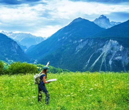 Traveler girl trekking in the mountains, searching right direction on the map, green picturesque valley, summer vacation, active lifestyle, travel and tourism concept photo
