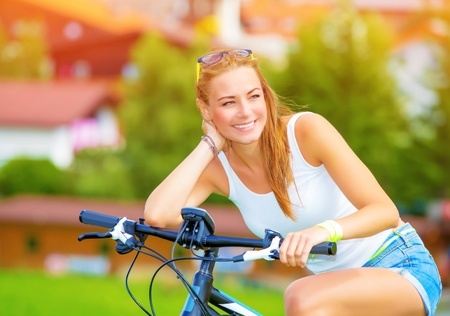 austrian village: Happy woman traveling on bicycle along Europe, active lifestyle, enjoying riding on pushbike, summer adventure, travel and tourism concept