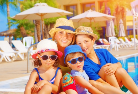 Mother with kids relaxing on beach resort, sitting near poolside, active summer holidays, young tourists, happy family concept Stock Photo