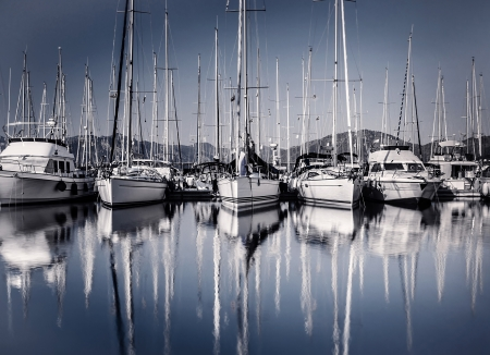 Sailboat harbor in evening, many luxury moored sail yacht in the port, ship mast reflected in water, marina in European city, summer holidays  Banco de Imagens