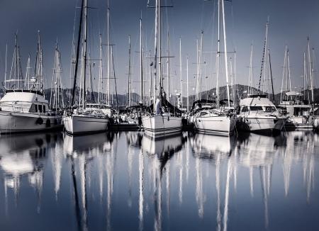 Zeilboot haven in de avond, vele luxe afgemeerd zeiljacht in de haven, het schip mast weerspiegeld in het water, de jachthaven in Europese stad, zomervakantie Stockfoto