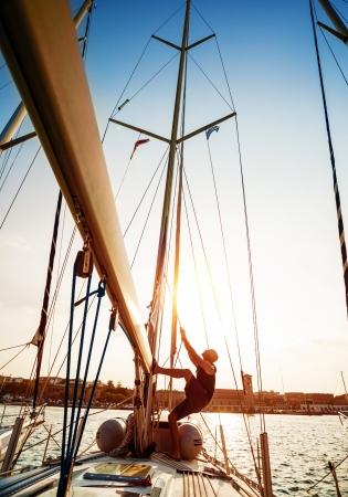 Young sailor working on sailboat, pulling rope, sailing sport, active lifestyle, captain on the ship, bright sunset light, summer adventure, travel concept photo