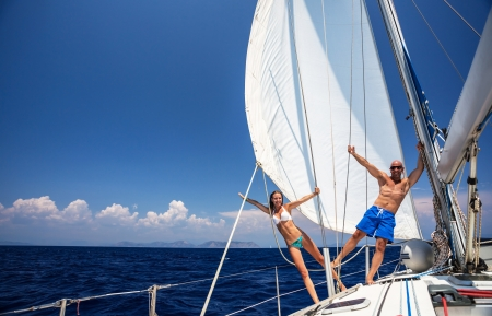 Happy couple having fun on sailboat, young family in water cruise, yachting sport, active lifestyle, summer vacation, romantic trip, travel and tourism concept  Stock Photo