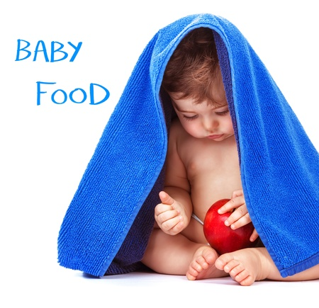 Adorable child sitting in the studio with red apple in hands and wrapped in blue towel, isolated on white background, little boy bathing, baby food concept  photo