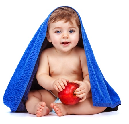 wrapped in a towel: Cute baby boy covered with blue towel holding in hands red fresh apple, sweet child after bath, healthy lifestyle, kids nutrition, happy childhood concept  Stock Photo