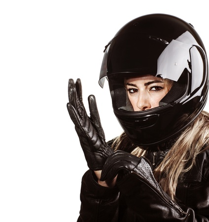 Closeup portrait of blond woman wearing motorsport outfit, isolated on white background, shiny black helmet and leather gloves, protective clothing  Stock Photo