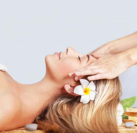 tratamiento facial: Primer plano de mujer rubia hermosa que se acuesta en la camilla, la vista lateral, masajista profesional, salón de spa de lujo, relajación y concepto de placer Foto de archivo
