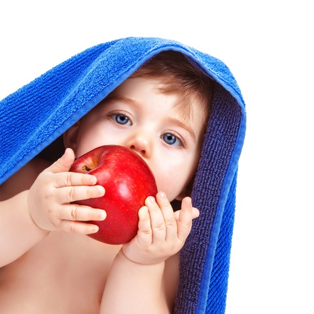 kids food: Closeup portrait of adorable toddler wrapped in blue towel, isolated on white background, baby boy biting red apple, infant after bath, healthy kids food