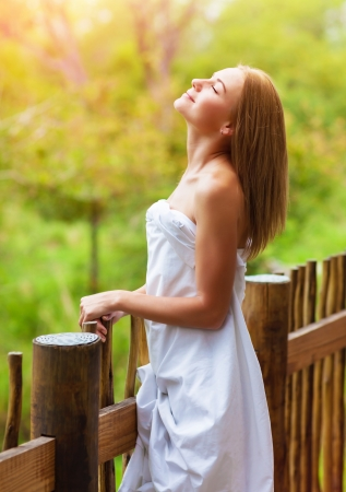 Pretty woman wrapped in white sheet standing on balcony in luxury spa hotel, enjoying peaceful nature, vacation and relaxation concept