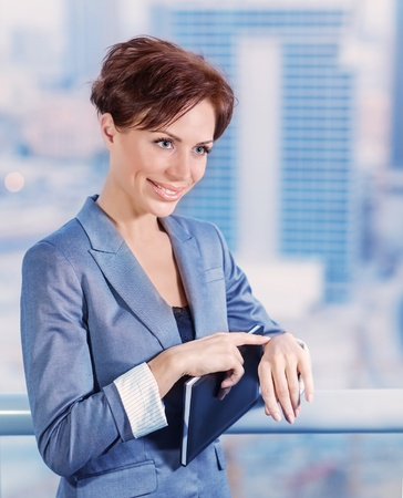 Closeup portrait of businesswoman waiting for someone, attractive female wearing elegant suit on cityscape background, success conception photo