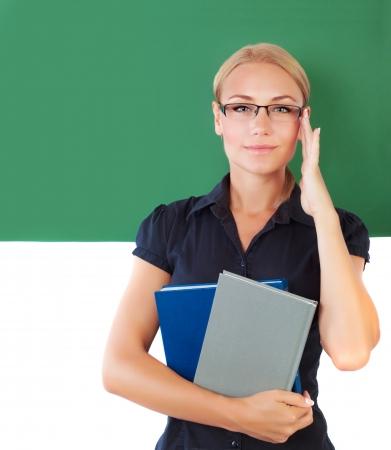 educators: Primer retrato de la joven y bella profesora, joven estudiante inteligente cerca de pizarra verde en la universidad, educador en la escuela, el concepto de la educación