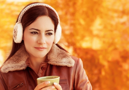 Closeup portrait of young beautiful woman drink coffee in autumnal park, wearing warm earmuff, happy lifestyle, fall concept