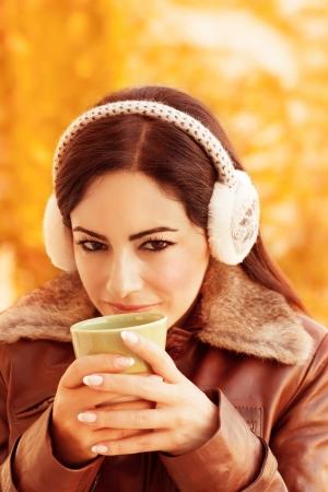earmuff: Closeup portrait of cute girl holding tea cup in hands on golden autumnal foliage background, wearing warm earmuff, autumn season concept