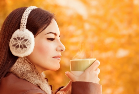 Side view of attractive female have coffee in autumnal park, gorgeous arabic girl wearing stylish head clothes on orange foliage background, autumn concept photo