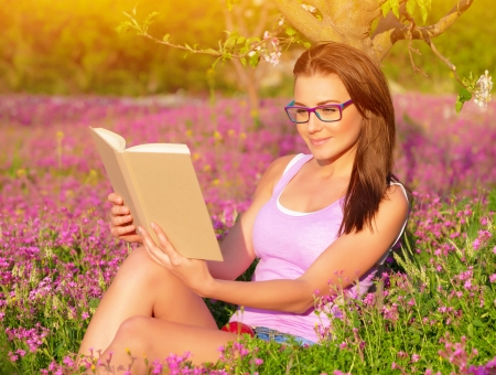 reading glasses: Attractive student girl sitting on pink floral field and read book, doing homework outdoors, wearing glasses, education concept