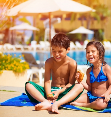 arabic boy: Two happy kids eating croissant near pool, having breakfast on the beach, active summer holidays, brother and sister enjoying sunny day, happiness concept