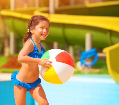 Active little girl playing with ball near pool, having fun in aquapark, water amusement, enjoying summer holidays, happiness concept photo