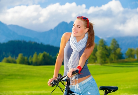 Portrait of cute cyclist girl resting in mountains, traveling on bicycle along Austrian mountains, enjoying beautiful nature, freedom concept photo