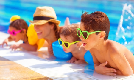 pool fun: Happy family in the pool, having fun in the water, mother with three kids enjoying aquapark, beach resort, summer holidays, pleasure concept