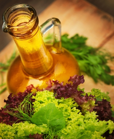 food dressing: Olive oil and fresh green vegetables on wooden table, tasty salad dressing, lettuce leaves, organic nutrition, healthy eating concept