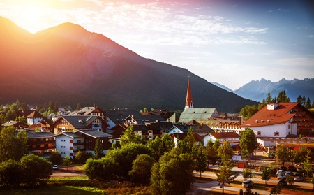 austrian village: Beautiful city in the mountains on sunset light, traditional European buildings, travel to Austria, summer holidays in Alpine mountains