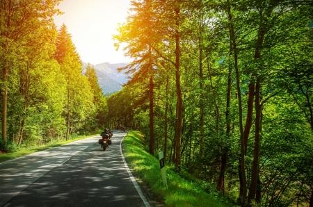 motociclista: Motorista en la carretera de montaña en la luz del atardecer, motociclista en carretera, moto en coche por los Alpes, viaje por Europa, hermoso bosque, estilo de vida activo