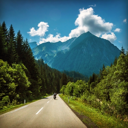 Motorcyclist riding on mountainous highway, Euro tour on motorbike, road pass along Alps mountains, extreme sport, freedom concept photo