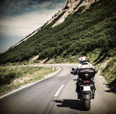 motociclista: Racer en la carretera de montaña, motorista a caballo por las montañas alpinas, viajar a Europa, las vacaciones de verano, deporte extremo
