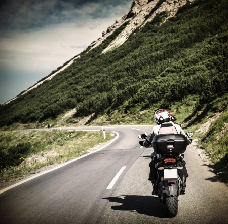 Racer on mountainous highway, biker riding along Alpine mountains, travel to Europe, summer vacation, extreme sport photo