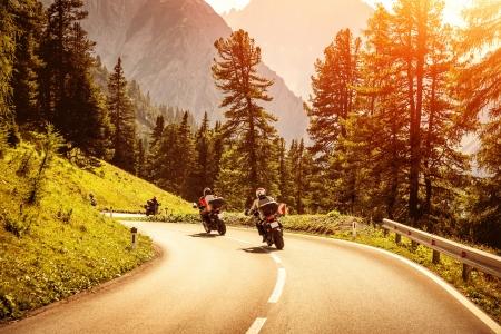 Groupe de motocyclistes à cheval sur les courbes route montagneuse, course de moto dans les Alpes, belle forêt de pins, lumière rouge coucher du soleil, concept de sport extrême Banque d'images - 22126615