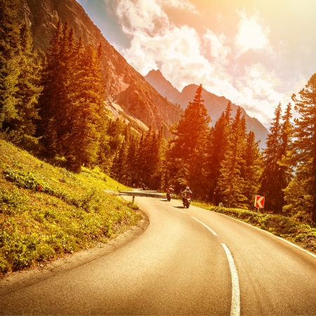 mountainous: Motorcyclists on the mountainous road in bright red sunset light, riding on highway pass along Alpine mountains, enjoying extreme sport, travel and tourism