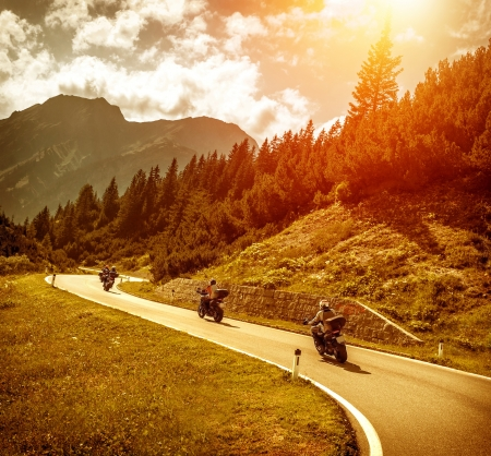 Group of motorcyclists riding on curves mountainous road, race of motorbike in Alps, beautiful pine forest, red sunset light, extreme sport concept photo