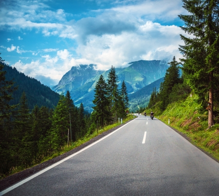 european alps: Group of bikers riding on road pass along Alpine mountains, travelers in Europe, mountainous highway, pine tree forest, extreme sport concept