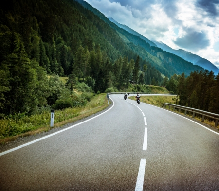 Group of bikers on mountainous road, fresh green forest, Alpine mountain, traveling on motorbike, active sport, speed concept photo