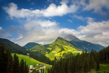 austrian village: Little village in the mountains, fresh green valley, traditional mountainous buildings, Alps, Europe, summer vacation, travel and tourism concept