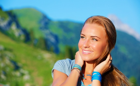 Closeup portrait of charming girl enjoying sunny day in Alpine mountains, having fun outdoors, trekking and hiking concept photo