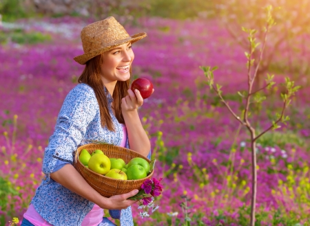harvest basket: Happy woman eating apple, cute girl holding in hands basket with fresh ripe apples, having fun on pink floral field, harvest season concept