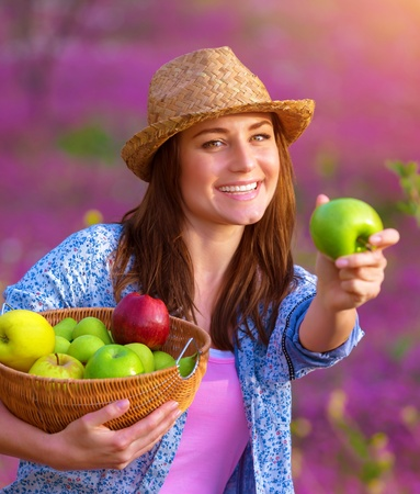 Happy young lady offers an apple, cute gardener girl holding in hands basket with fresh ripe fruits, spending time on backyard, healthy lifestyle photo