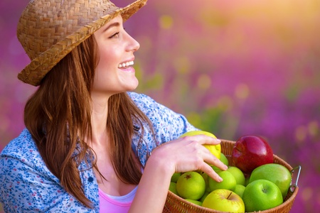 Side view of attractive cheerful female holding in hands basket with apples, fresh ripe fruits, sunset light, pink floral field, harvest season photo